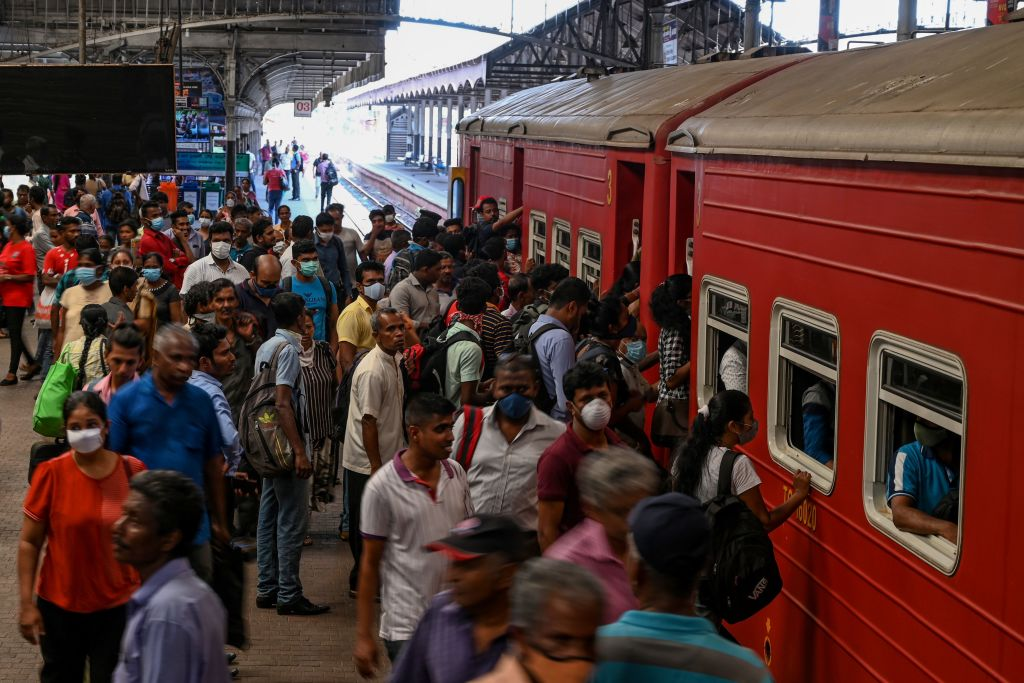 FILE PHOTO: Commuters board on a train to travel to provinces, after the authorities announced a weekend curfew in the country as a preventive measure against the spread of the COVID-19 novel coronavirus, at a main railway station in Colombo on March 20, 2020. (Photo by LAKRUWAN WANNIARACHCHI/AFP via Getty Images)