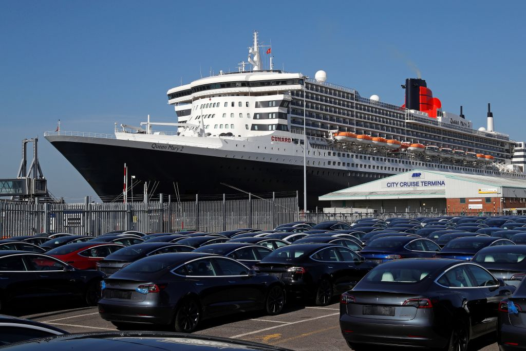 A British transatlantic ocean liner, sits moored alongside a vehicle storage area full of new Tesla electric cars, at The Western Docks in Southampton on April 20, 2020. (Photo by ADRIAN DENNIS/AFP via Getty Images)