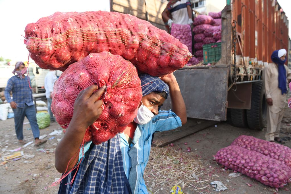 FILE PHOTO: Labourers unload sacks of onions from a truck on the International Labour Day at a vegetable wholesale market during a government-imposed nationwide lockdown as a preventive measure against the spread of the COVID-19 coronavirus, on the outskirts of Amritsar on May 1, 2020. (Photo by NARINDER NANU/AFP via Getty Images)