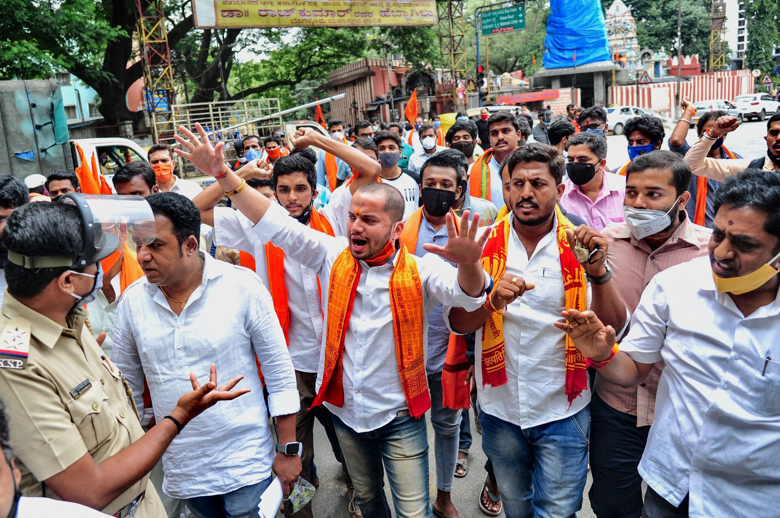 """A policeman (L) gestures towards activists of Hindu religious organisation 'Bajrang Dal' during a protest against the violence that broke out in Devara Jevana Halli in Bangalore on August 13, 2020, after a """"derogatory"""" Facebook post about the Prophet Mohammed sparked riots.(Photo by Manjunath Kiran / AFP)"""