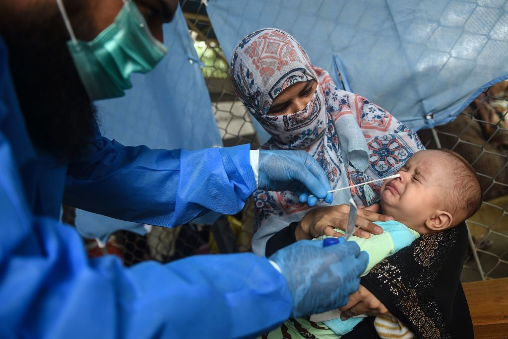 In this picture taken on September 1, 2020, a health official takes a swab sample from a child to test for the COVID-19 coronavirus at a testing site in Karachi. (Photo by RIZWAN TABASSUM/AFP via Getty Images)