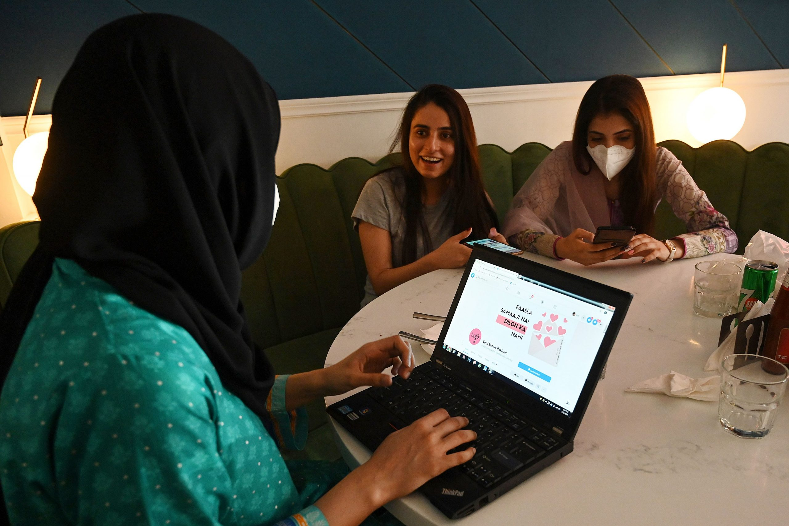 Women discuss as they check out the social online group 'The Soul Sisters Pakistan' on their Facebook page, in Lahore. (Photo by ARIF ALI/AFP via Getty Images)