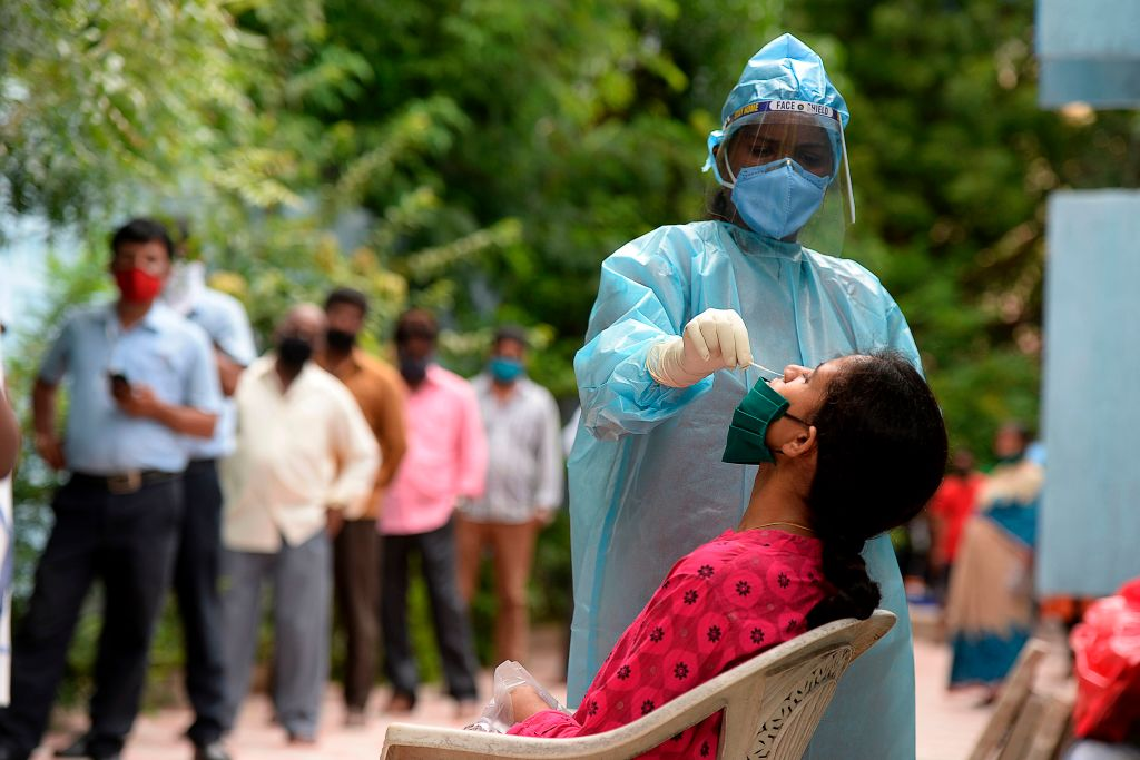 Residents stand in a queue to register their names as a health worker (R) wearing Personal Protective Equipment (PPE) suit collects a swab sample from a woman to test for the Covid-19 coronavirus, at a primary health centre in Hyderabad on September 4, 2020. (Photo by NOAH SEELAM/AFP via Getty Images)
