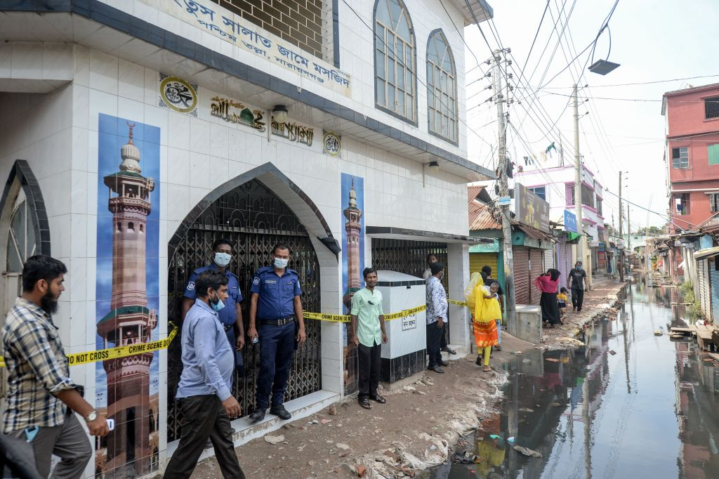 Police personnel stand guard in front of a mosque, following a fire accident, in Narayanganj on September 6, 2020. A suspected gas explosion in a mosque just outside the Bangladesh capital has killed 24 people with a dozen more fighting for their life with critical burn injuries, officials said. (Photo by MUNIR UZ ZAMAN/AFP via Getty Images)