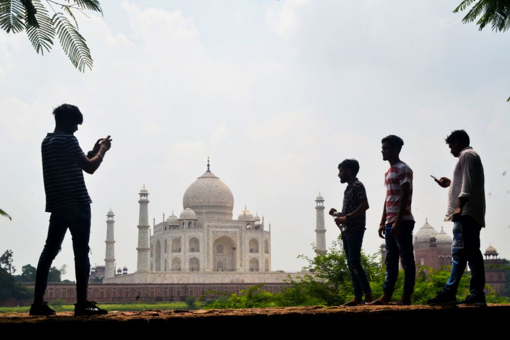 People take pictures with their mobile phones near the Taj Mahal in Agra on September 8, 2020. India's top tourist attraction the Taj Mahal is set to reopen more than six months after it was shut, officials said on September 8, even as the vast nation battles soaring coronavirus infections. (Photo by PAWAN SHARMA/AFP via Getty Images)