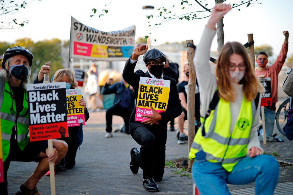 Protesters from Black Lives Matter take a knee as they gather outside the US Embassy in London on September 11, 2020, the day of a trial hearing of the four police officers charged with the murder of George Floyd in the US. (Photo by TOLGA AKMEN/AFP via Getty Images)