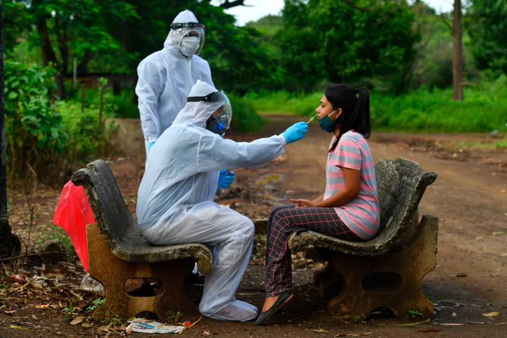 Medical staff wearing Personal Protective Equipment (PPE) take a nasal swab sample from a woman during a Covid-19 Coronavirus screening outside a quarantine centre, in Nashik on September 13, 2020.(Photo by INDRANIL MUKHERJEE/AFP via Getty Images)