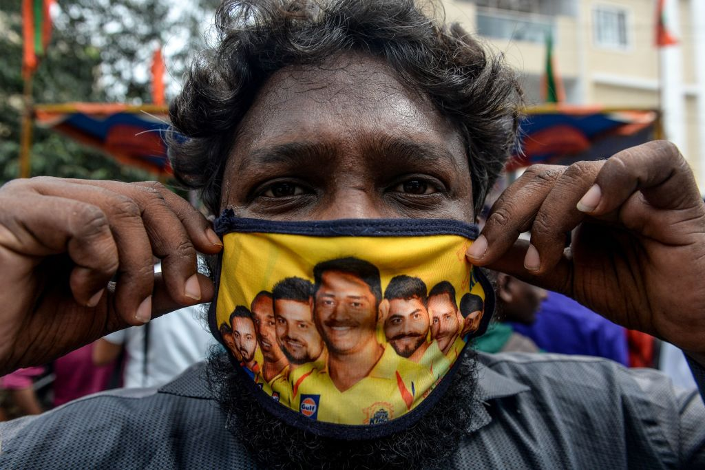 A man in Chennai shows off his facemask decorated with portraits of Chennai Super Kings, which won the IPL opener against Mumbai Indians, ahead of the match.  (Photo: ARUN SANKAR/AFP via Getty Images)