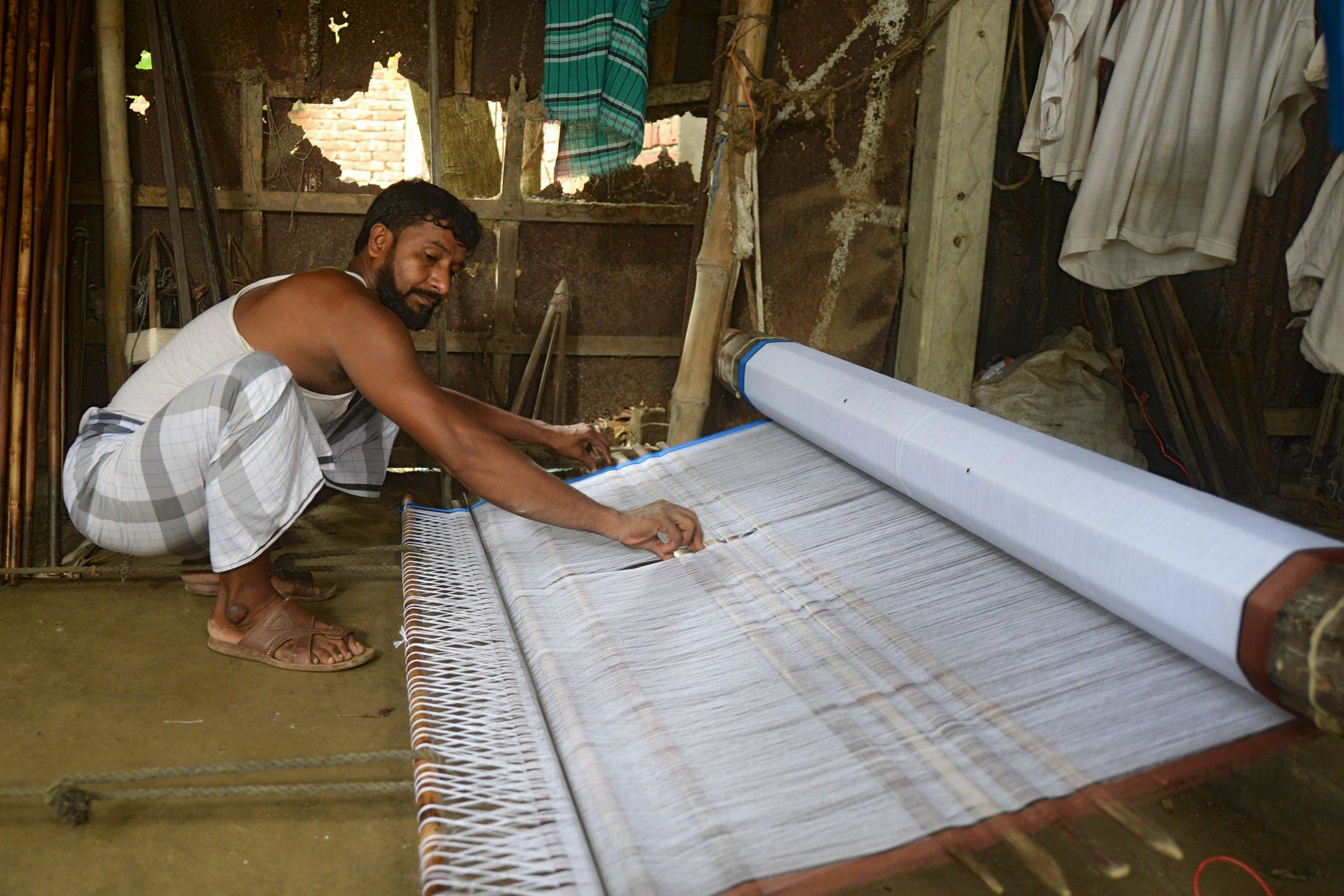 In this picture taken on September 15, 2020, a weaver prepares threads to make fabric with a handloom in Ruhitpur on the outskirts of Dhaka. - In small tin sheds in a rural town just outside Bangladesh's capital Dhaka, wooden looms are deftly operated by a group of men and women -- among the country's last traditional weavers as huge garment factories churn out cheaper alternatives. The South Asian nation's centuries-old traditional weaving was once highly sort after, with nobility from Asia and Europe wearing the fine Muslin clothing. (Photo by Munir UZ ZAMAN / AFP) (Photo by MUNIR UZ ZAMAN/AFP via Getty Images)