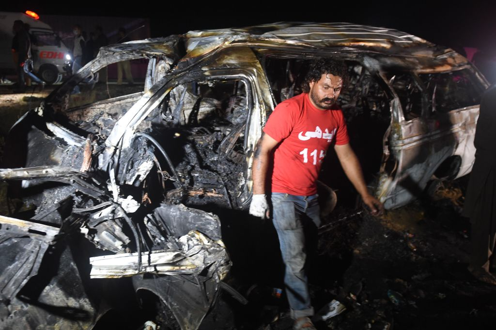 A volunteer walks past a burnt passenger van following an overnight accident in the Nooriabad area on a highway some 50 kilometers from Pakistan's port city of Karachi late on September 26, 2020.(Photo by Rizwan TABASSUM / AFP) (Photo by RIZWAN TABASSUM/AFP via Getty Images)