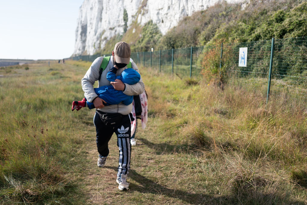 A father carries his small child shortly after landing on September 15, 2020 at Kingsdown Beach in Deal, England. More than 6,100 migrants have made the crossing by boat this year according to an analysis by the Press Association. (Photo by Luke Dray/Getty Images)