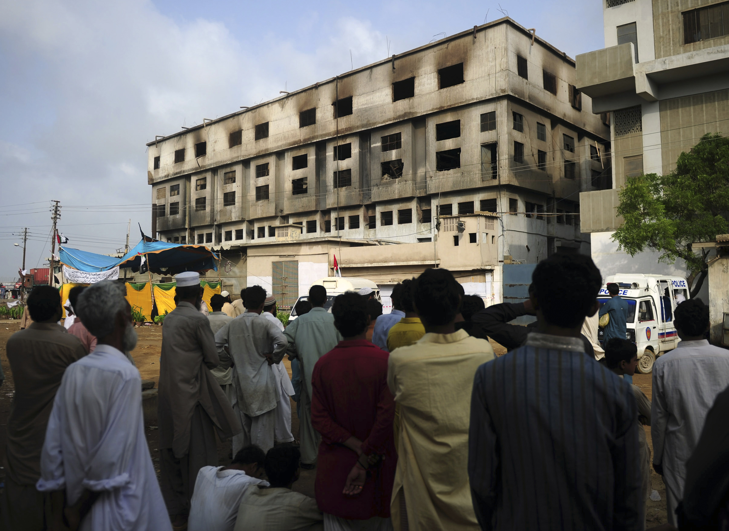 Bystanders look on outside the burnt-out garment factory in Karachi on September 14, 2012.  (ASIF HASSAN/AFP/GettyImages)