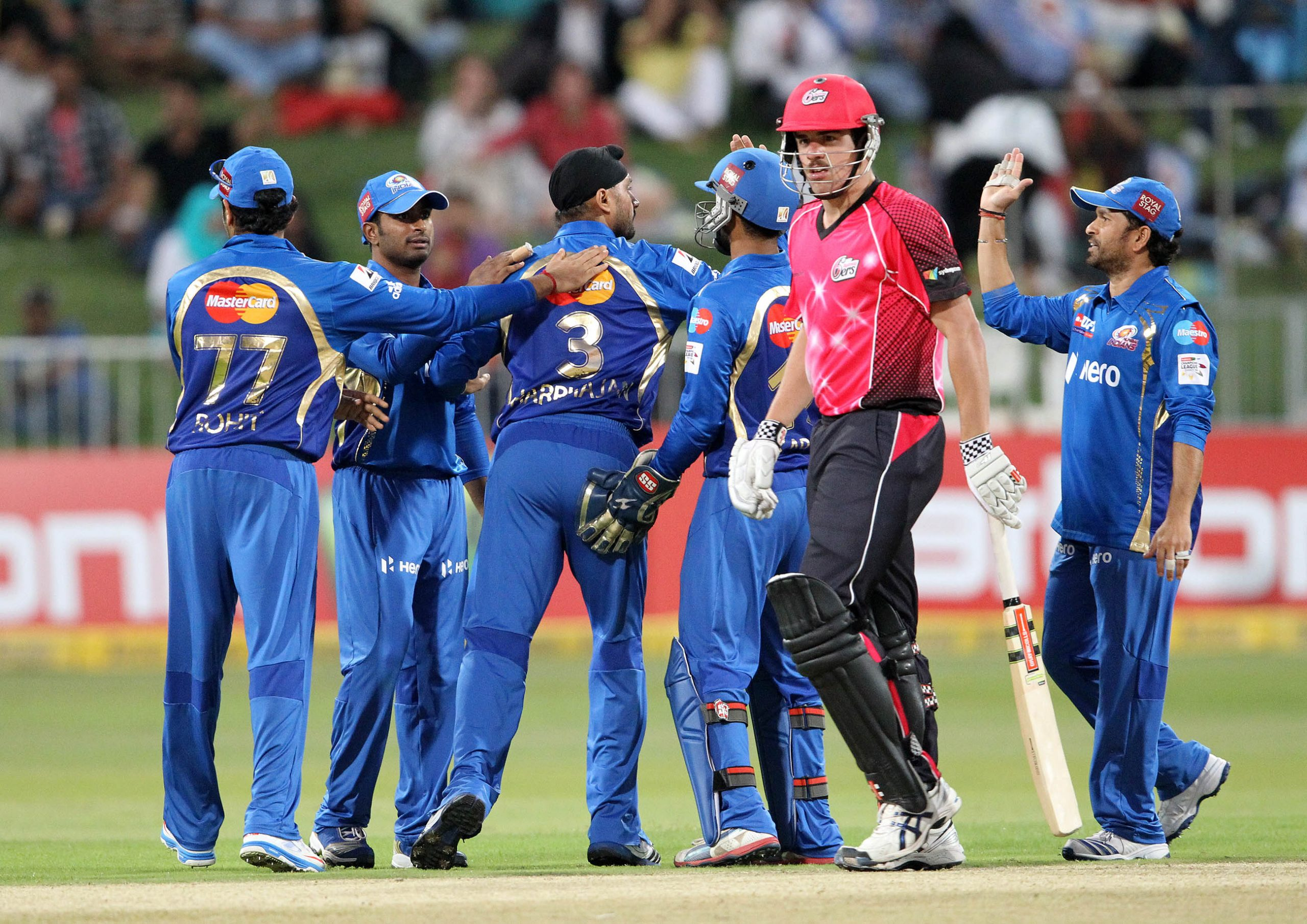 Moise Henriques of the Sydney Sixers walks off as the Mumbai Indians celebrate his wicket on October 22, 2012 during a Champions League T20 (CLT20) match Sydney Sixers vs Mumbai Indians at Sahara Stadium Kingsmead in Durban. AFP PHOTO / STR        (Photo credit should read -/AFP via Getty Images)
