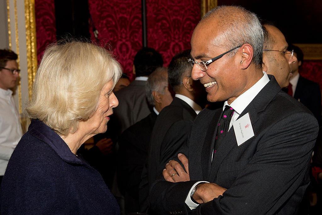 FILE PHOTO: Britain's Camilla, Duchess of Cornwall talks to British journalist and BBC news presenter, George Alagiah (R) who was born in Sri Lanka, during a reception in Clarence House, central London on October 24, 2013. (LEON NEAL/AFP via Getty Images)