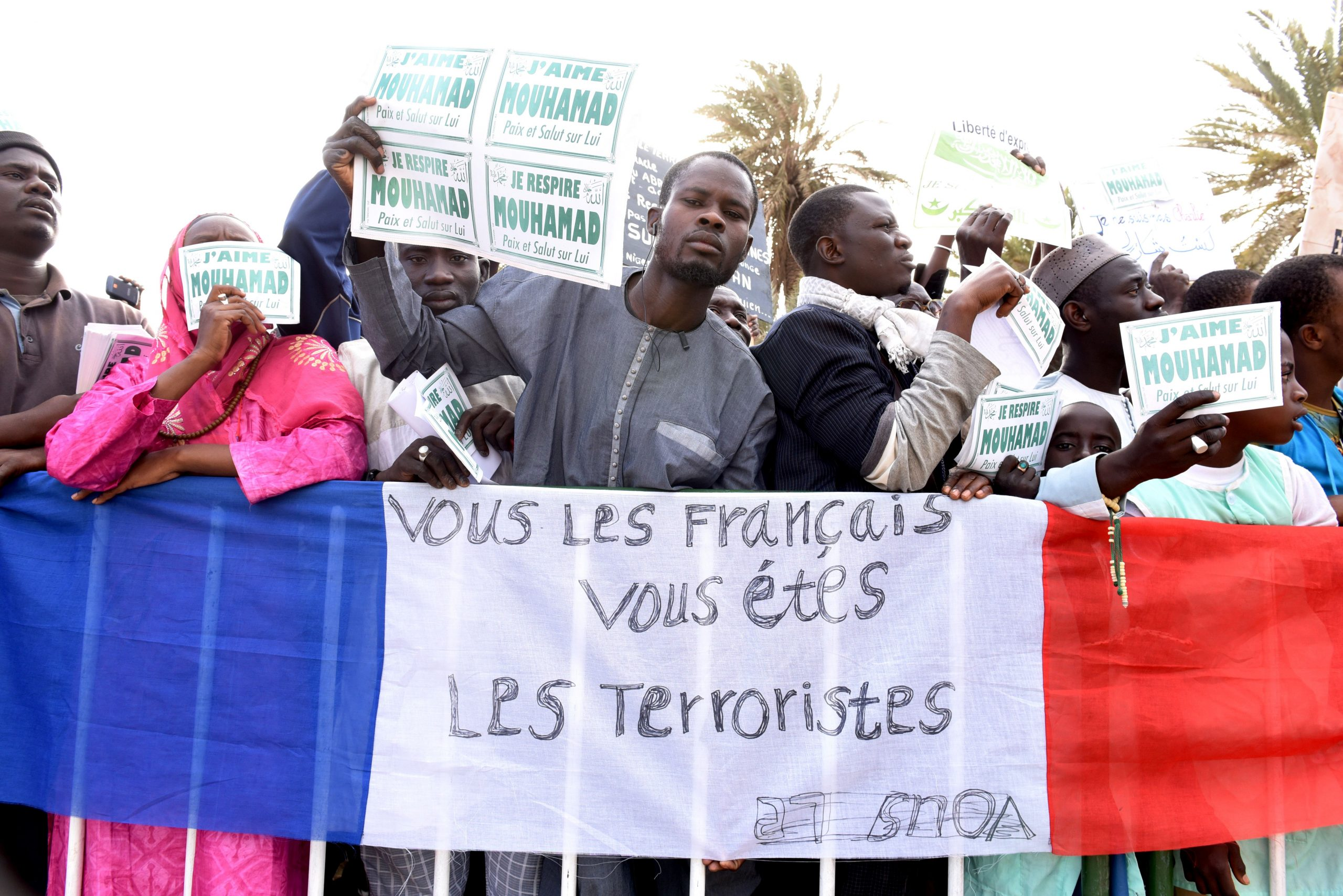 "People hold placards reading in French ""I breath Mouhamad. Peace and Salvation on Him"" and ""I love Mouhamad. Peace and Salvation on Him"" in front of a French flag with an inscription on it reading in French ""French you are the terrorists"" on January 24, 2015 during a rally in Dakar to protest against French weekly Charlie Hebdo's publication of a cartoon of the Prophet Mohammed. (SEYLLOU/AFP via Getty Images)"