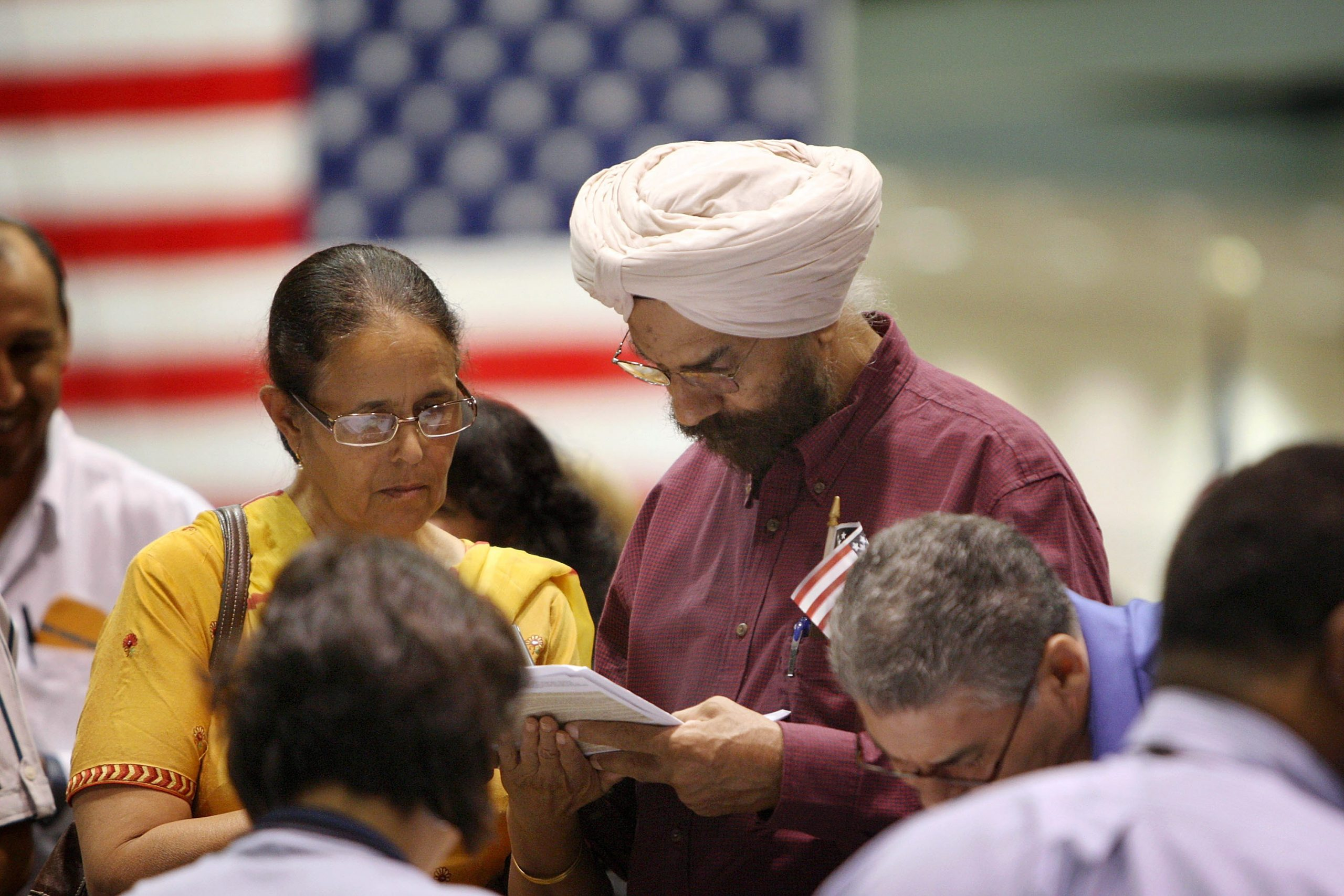 LOS ANGELES, CA - AUGUST 28:  Amrik Sidhu (R) and his wife Harjinder Sidhu, both Sikhs from India, apply for their passports after gaining US citizenship as 18,418 people are sworn in as US citizens during naturalization ceremonies at the Los Angeles Convention Center on August 28, 2008 in Los Angeles, California. Immigrants, especially Latinos, which now make up 15 percent of the US population, play an increasingly important role in US politics. Democratic presidential candidate Barack Obama (D-IL), who could benefit from a strong Hispanic following of former presidential hopeful Sen. Hillary Clinton (D-NY), who now campaigns for him, has set aside $20 million for Latino outreach. Republican rival John McCain has also stepped up efforts to attract Latinos, focusing particularly on those in the military. The US Department of Homeland Security reports that citizenship applications have jumped by more than 100 percent since 2006, a surge in naturalization that is expected to add to the 17 million existing eligible Latino voters nationwide and lead to an anticipated record of 9.2 million Latinos voting in the November presidential election. Issues of interest to Latinos include the slumping economy, employment, health care, housing, and immigration reform.  (Photo by David McNew/Getty Images)