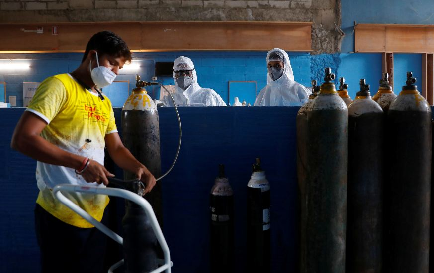 A worker refills an oxygen cylinder as medical workers wait at the Yatharth Hospital in Noida, on the outskirts of New Delhi, India, September 15, 2020. Picture taken September 15, 2020. REUTERS/Adnan Abidi