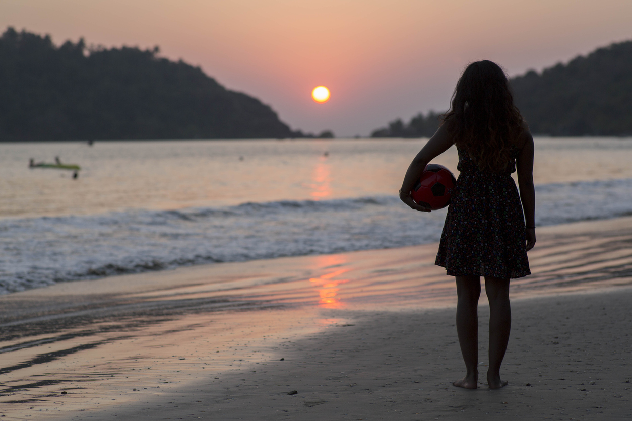 A silhouette of a girl standing on the beach with a ball under her arm watching the sunset over the ocean in Goa, India