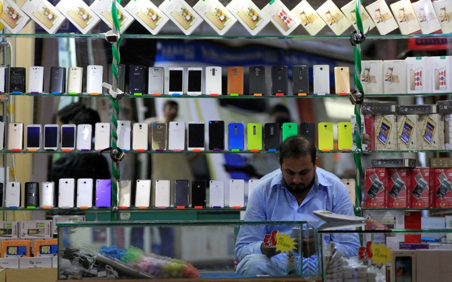 FILE PHOTO: A shopkeeper plays with his mobile phone at a phone market in Rawalpindi, Pakistan July 4, 2017. REUTERS/Caren Firouz/File Photo