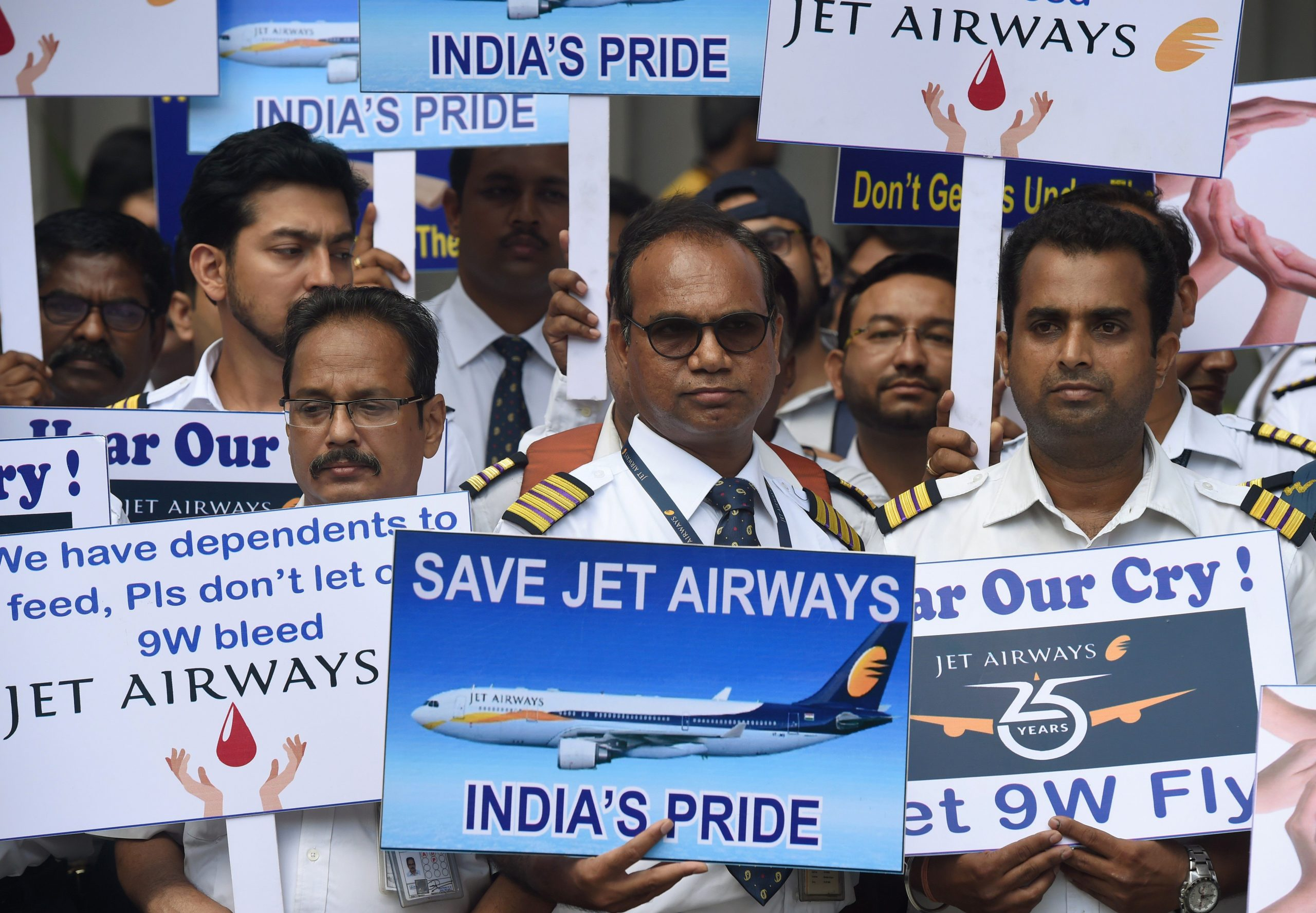 India's Jet Airways employees hold placards during a silent protest in Mumbai on May 8, 2019. - India's debt-stricken Jet Airways halted all of its operations last month after failing to secure emergency funding from lenders, leaving it teetering on the edge of bankruptcy. (Photo by PUNIT PARANJPE / AFP)        (Photo credit should read PUNIT PARANJPE/AFP via Getty Images)