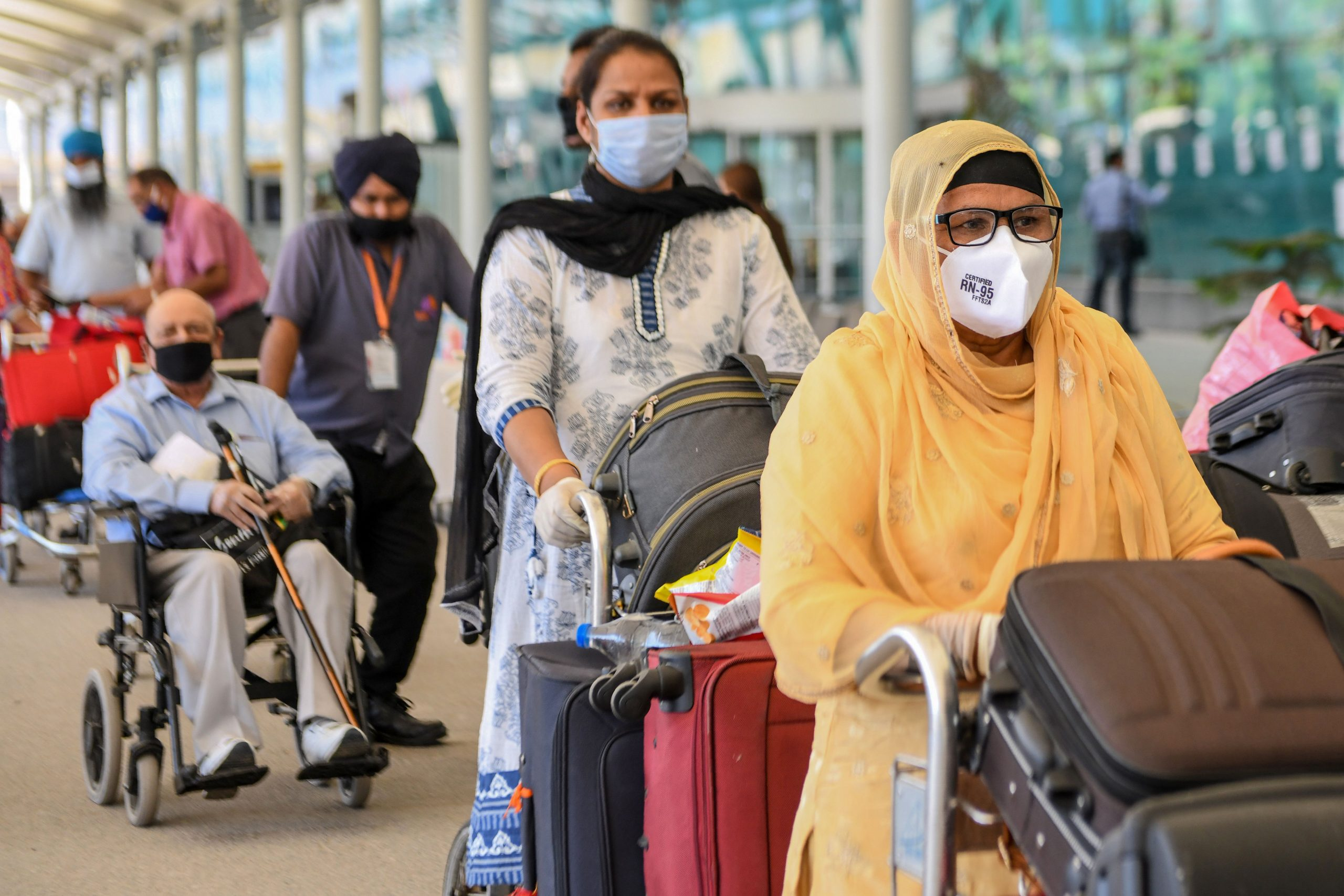 British nationals queue before checking-in for a special flight to London after the government eased a nationwide lockdown imposed as a preventive measure against the COVID-19 coronavirus, at Sri Guru Ram Dass Jee International Airport on the outskirts of Amritsar on May 15, 2020. (Photo by NARINDER NANU / AFP) (Photo by NARINDER NANU/AFP via Getty Images)