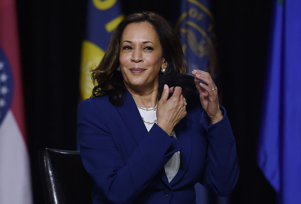 Democratic vice presidential candidate  Kamala Harris removes her mask before speaking during the first press conference with Joe Biden in Wilmington, Delaware, on August 12, 2020. (Photo by OLIVIER DOULIERY/AFP via Getty Images)