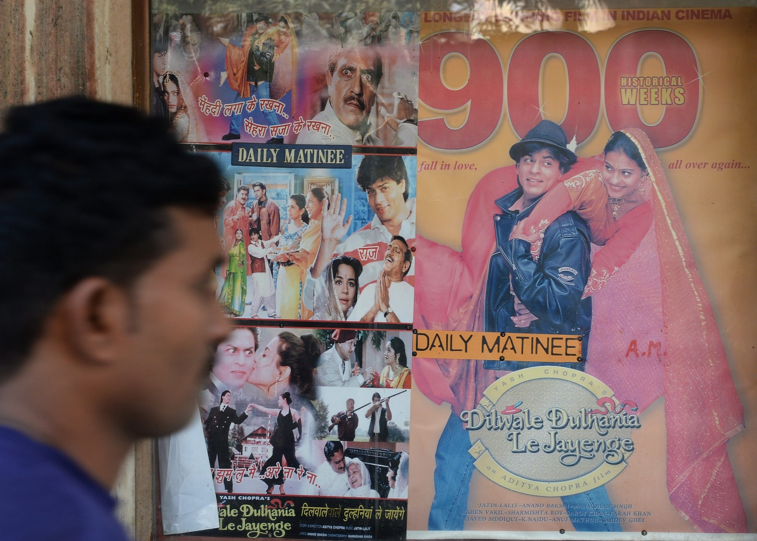 """TO GO WITH India-entertainment-Bollywood-cinema,FOCUS by Aditya PHATAK In this photograph taken on December 5, 2014, an Indian cinemagoer walks past a poster of a screening of the popular Bollywood Hindi film 'Dilwale Dulhania Le Jayenge' (The Brave hearted Will Take The Bride Away) at the Maratha Mandir movie theatre in Mumbai.  The 1995 Bollywood love flick titled Dilwale Dulhaniya Le Jayenge (The Brave Hearted Will Take Away the Bride) is now the longest running movie in Indian cinema history. """"DDLJ"""", as the movie is commonly known in India, is set to clock a successful run of 1000 weeks on December 12.   AFP PHOTO / INDRANIL MUKHERJEE        (Photo credit should read INDRANIL MUKHERJEE/AFP via Getty Images)"""