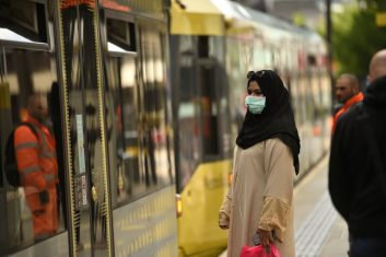 Coronavirus - A commuter wears a protective facemask as she waits at a tram-stop in central Manchester on June 5, 2020- Face coverings will soon be compulsory for people wanting to travel on public transport. (Photo: OLI SCARFF/AFP via Getty Images)