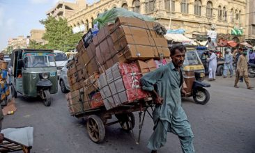 HEADLINE STORY - A labourer drags his loaded cart on a street near a market in the Pakistan's port city of Karachi on June 11, 2020. (Photo by RIZWAN TABASSUM/AFP via Getty Images)