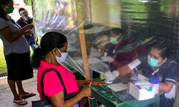 News - An election official behind a plastic sheet marks the finger of a voter (2L) with ink during a mock election to test the guidelines implemented against the COVID-19 coronavirus in Ingiriya of Kalutara District in Western Province on June 14, 2020. (Photo by LAKRUWAN WANNIARACHCHI/AFP via Getty Images)