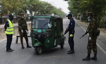BANGLADESH - Policemen and army personnel stop a motorist at checkpoint along a road during a government imposed shutdown as a preventative measure against the COVID-19 coronavirus, in Narayanganj on the outskirts of Dhaka on April 8, 2020. (Photo by MUNIR UZ ZAMAN / AFP) (Photo by MUNIR UZ ZAMAN/AFP via Getty Images)