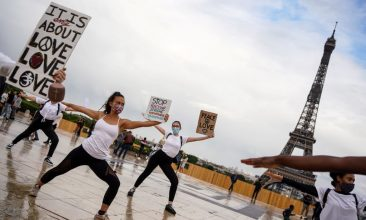 News - Members of Hermine Prunier's yoga group hold up placards as they perform a choreography to an Indian song for world peace and protest to show their support for the Black Lives Matter movement on the Parvis des droits de l'homme, place du Trocadero, in Paris on June 21, 2020, during the French Festival of Music. (Photo: ABDULMONAM EASSA/AFP via Getty Images)
