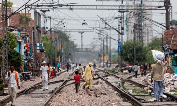 INDIA - Residents walk along the train tracks in Azadpur area after the government eased a nationwide lockdown imposed as a preventive measure against the spread of the COVID-19 coronavirus, in New Delhi on June 26, 2020. (Photo by XAVIER GALIANA/AFP via Getty Images)