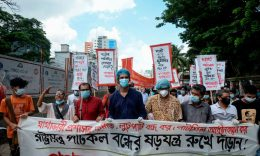 BANGLADESH - Bangladesh's left wing party supporters walk behind a banner during a protest against the shutdown of a state-owned jute mill in Dhaka on July 1, 2020. (Photo by MUNIR UZ ZAMAN/AFP via Getty Images)