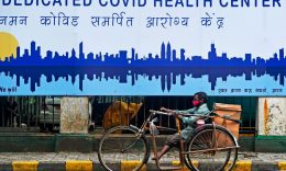 Coronavirus - A physically challenged man rides a tricycle in front of a COVID-19 coronavirus health center in Mumbai on July 7, 2020. (Photo by PUNIT PARANJPE/AFP via Getty Images)
