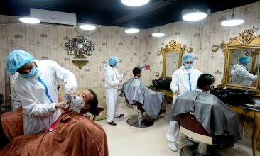 BANGLADESH - Barbers wearing protective cloths give to their clients a haircut at a barber shop amid concerns over the spread of the COVID-19 coronavirus, in Dhaka on July 7, 2020. (Photo by MUNIR UZ ZAMAN/AFP via Getty Images)
