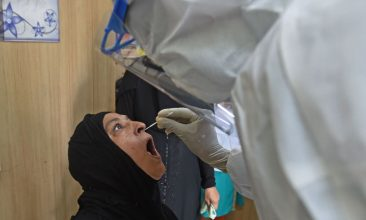 Coronavirus - A health worker wearing personal protective equipment (PPE) gear collects a nasal swab with a rapid antigen test (RAT) for the COVID-19 coronavirus, at Urban Health Centre in Ahmedabad on July 10, 2020. (Photo by SAM PANTHAKY/AFP via Getty Images)