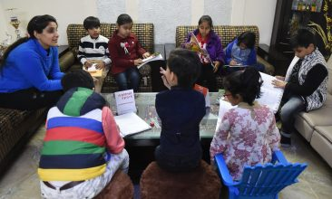 """FEATURES - In this photograph taken on February 13, 2019, Ruchi Taneja (L) teaches a group of Indian children studying with an app created by Planet Sparks that uses """"gamified"""" teaching methods at a tuition centre in New Delhi. - From a multi-billion-dollar education startup to wired-up mannequins, technology is helping to revolutionise the way Indian schoolchildren are learning -- provided their parents can afford it. (Photo by Money SHARMA / AFP) / To go with 'INDIA-ECONOMY-EDUCATION-TECHNOLOGY-AMAZON-BYJU',FOCUS by Vishal MANVE        (Photo credit should read MONEY SHARMA/AFP via Getty Images)"""