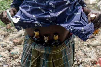 Coronavirus - A man shows bottles of alcohol, stuck under his waistband, bought from a liquor shop after the government eased a nationwide lockdown imposed as a preventive measure against the COVID-19 coronavirus, on the outskirts of Chennai on May 7, 2020.(Photo by ARUN SANKAR/AFP via Getty Images)