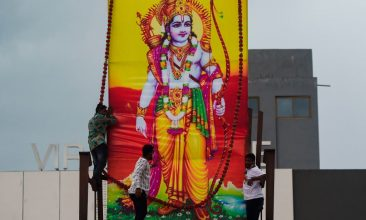 Ayodhya - Workers erect a large poster of Hindu Lord Ram on the roof of a service station in Vadodara, Gujarat, on August 5, 2020, to celebrate the groundbreaking ceremony of the Ram Temple in Ayodhya. (Photo by PUNIT PARANJPE/AFP via Getty Images)