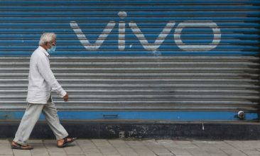 CRICKET - A pedestrian walks past an advertisement of Chinese mobile phone maker Vivo painted on the shutters of a closed shop at a market in Mumbai . (Photo: INDRANIL MUKHERJEE/AFP via Getty Images)