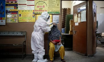 Coronavirus - A health worker in personal protective equipment (PPE) collects a sample using a swab from a person at a local health centre to conduct tests for the coronavirus disease (COVID-19) in New Delhi, India August 7, 2020. REUTERS/Adnan Abidi