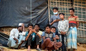 News - Rohingya refugees watch on a mobile phone a live feed of Myanmar's State Counsellor Aung San Suu Kyi's appearance at the UN's International Court of Justice in the Hague in the Netherlands, on the second day of her hearing on the Rohingya genocide case, in a refugee camp in Cox's Bazar in southern Bangladesh on December 11, 2019. - (Photo by MUNIR UZ ZAMAN/AFP via Getty Images)