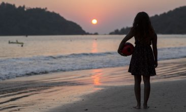 FEATURES - A silhouette of a girl standing on the beach with a ball under her arm watching the sunset over the ocean in Goa, India