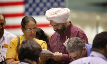 US Elections - LOS ANGELES, CA - AUGUST 28:  Amrik Sidhu (R) and his wife Harjinder Sidhu, both Sikhs from India, apply for their passports after gaining US citizenship as 18,418 people are sworn in as US citizens during naturalization ceremonies at the Los Angeles Convention Center on August 28, 2008 in Los Angeles, California. Immigrants, especially Latinos, which now make up 15 percent of the US population, play an increasingly important role in US politics. Democratic presidential candidate Barack Obama (D-IL), who could benefit from a strong Hispanic following of former presidential hopeful Sen. Hillary Clinton (D-NY), who now campaigns for him, has set aside $20 million for Latino outreach. Republican rival John McCain has also stepped up efforts to attract Latinos, focusing particularly on those in the military. The US Department of Homeland Security reports that citizenship applications have jumped by more than 100 percent since 2006, a surge in naturalization that is expected to add to the 17 million existing eligible Latino voters nationwide and lead to an anticipated record of 9.2 million Latinos voting in the November presidential election. Issues of interest to Latinos include the slumping economy, employment, health care, housing, and immigration reform.  (Photo by David McNew/Getty Images)