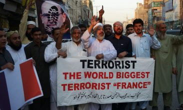 HEADLINE STORY - Traders shout slogans as they hold a banner and a poster of French Prime Minister Jean Castex, with a footprint over his face, during a protest following French President Emmanuel Macron's comments over the Prophet Mohammed caricatures, in Peshawar on October 26, 2020. Photo (Photo by ABDUL MAJEED/AFP via Getty Images)
