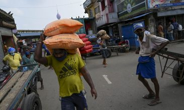 News - A labourer carries sacks at a market in Colombo on October 29, 2020 after a three-day curfew was announced from October 30 to contain the spread of the Covid-19 coronavirus. (Photo by ISHARA S. KODIKARA / AFP) (Photo by ISHARA S. KODIKARA/AFP via Getty Images)