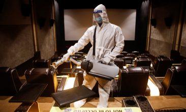 Coronavirus - A man in personal protective equipment (PPE) sanitizes a cinema hall before a movie amid the spread of the coronavirus disease (COVID-19) in Mumbai, India November 15, 2020. REUTERS/Francis Mascarenhas