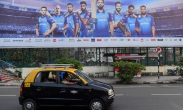 CRICKET - In this picture taken on October 10, 2020, a taxi drives past a hoarding of Mumbai Indians cricketers of the Indian Premier League (IPL) cricket tournament in Mumbai. - Unable to bet legally, tens of millions of Indian cricket fans have turned to fantasy games based on the Indian Premier League, which have exploited a loophole to create a billion-dollar industry. (Photo by Indranil MUKHERJEE / AFP) / To go with 'CRICKET-IND-IPL-FANTASY-INDIA', FOCUS by Vishal MANVE with Faisal KAMAL in Delhi (Photo by INDRANIL MUKHERJEE/AFP via Getty Images)