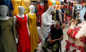 HEADLINE STORY - A health worker wearing protective gear collects a swab sample from a man during a medical screening for the Covid-19 coronavirus at a garment wholesale market in Mumbai on November 20, 2020.(Photo by PUNIT PARANJPE/AFP via Getty Images)
